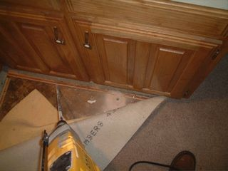 Here we pulled back the carpet and drilled around the wet bar area. Drilling or wall foaming is required around plumbing areas because the pipes provide access through your foundation and moisture. Termite product will be applied to the soil using this hole. Not treating all plumbing areas would be a mistake.